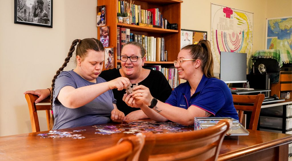 A mother and daughter sit down to do a puzzle with their HenderCare support worker.